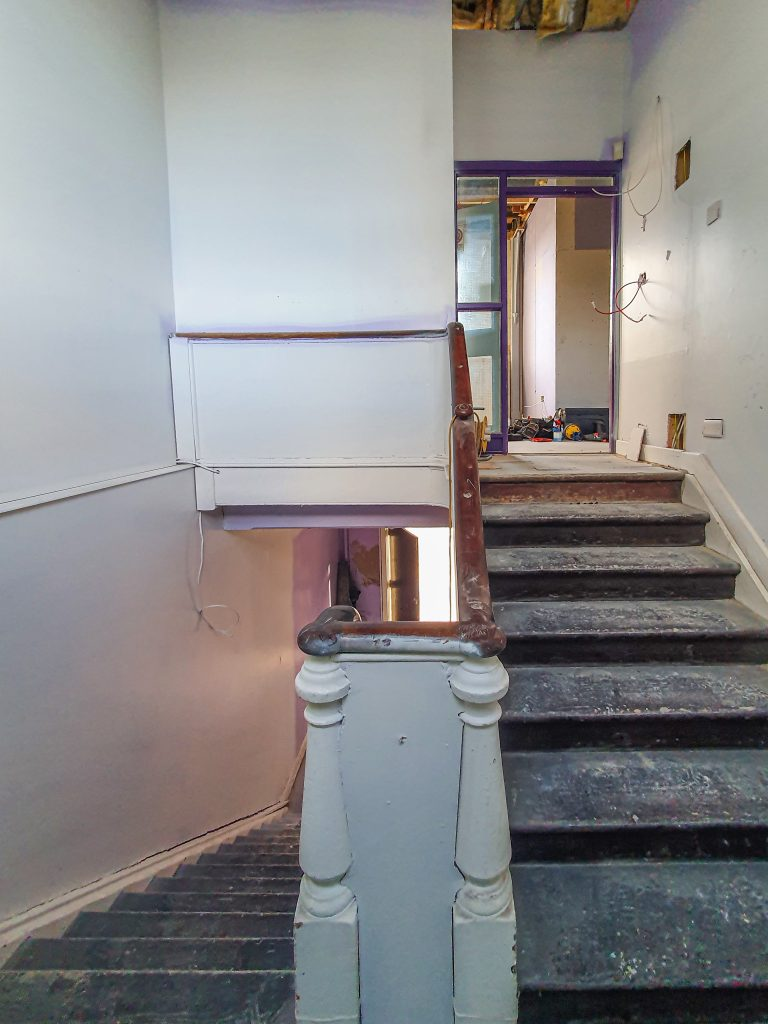 View from the landing between the ground and first floors of Farset Labs. Wooden staircase will be restored.